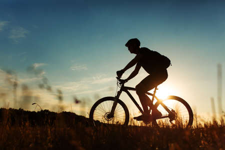 biker man: Silhouette of a biker on sky background on sunset with focus on bike Stock Photo