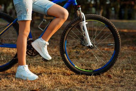 Urban biking - teenage girl with bike in the city park