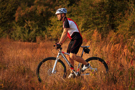 red mountain: Man in a red t-shirt is riding a sport bicycle in the field on green background