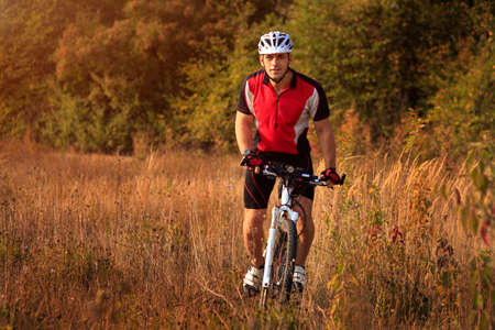 red tshirt: Man in a red t-shirt is riding a sport bicycle in the field on green background