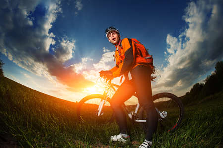 off road biking: biker in green summer field with blue sky and clouds on background