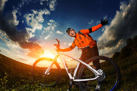 rapidity: Man Cyclist in Orange Jersey with bike on sunset