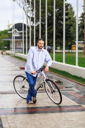 clavados: personas, estilo, ocio y estilo de vida - hombre inconformista joven con la bici de piñón fijo en la calle de la ciudad