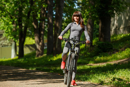 recreational: Healthy and happy cyclist woman riding fast a bicycle in a park