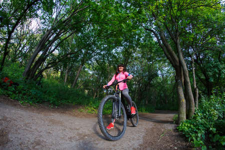 alternative transport: Pretty Young woman having fun riding a bicycle in the park. Green concept of alternative transport preserving and saving environment matters