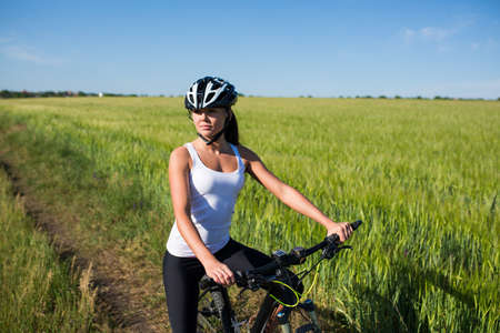 rides: girl in helnet rides a bicycle in the countryside. Healsy lifestyle concept.