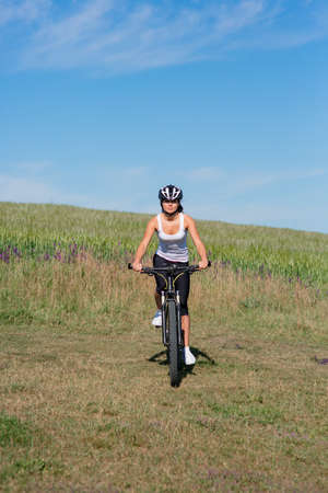 relaxion: Happy Young Woman riding bicycle outside against blue sky. Healthy Lifestyle.