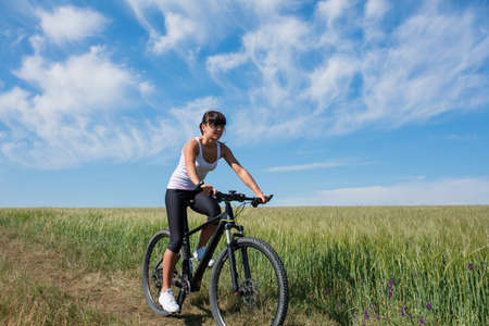 healthy sport: Sport bike woman on a meadow with a beautiful landscape. Healthy lifestyle
