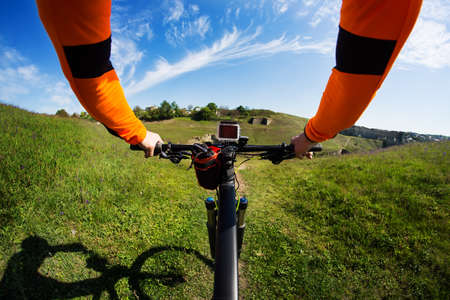 handlebar: Hands in orange jacket holding handlebar of a bicycle with green meadow on background Stock Photo