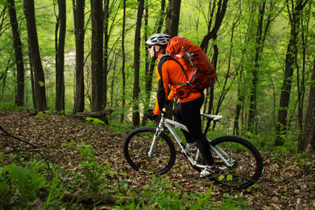 Biker with backpack on the forest road Stock Photo