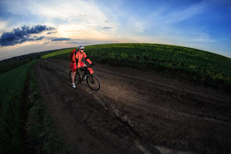 rapidity: Man on mountain bike rides on the trail on a beautiful sunset. Wide view