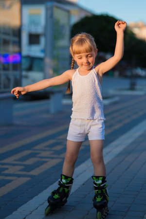 back alley: Little pretty girl rides on roller skates at a park on sunset Stock Photo