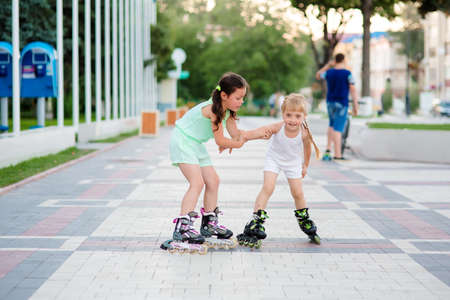 rollerblades: two beautiful little sisters in a roller skates ride on the street