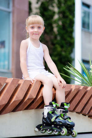 roller blade: Little girl on roller skates at park on a sunny day sitting on the bench Stock Photo