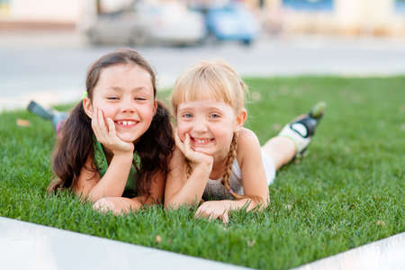 lawn grass: Two little sisters having fun in summer park while laying on lawn.