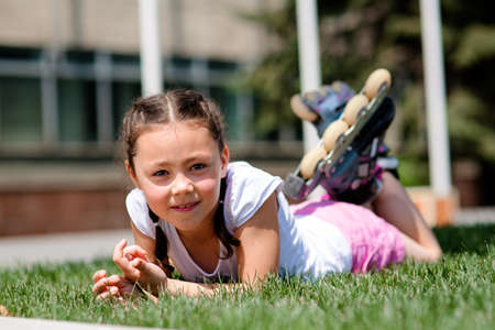 Little girl in rollers is laying on the lawn in the park having rest