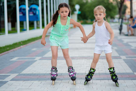 kneepad: two beautiful little sisters in a roller skates ride on the street