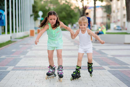 rollerskater: two beautiful little sisters in a roller skates ride on the street