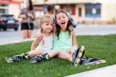 kneepad: two beautiful little sisters in a roller skates sit on the street