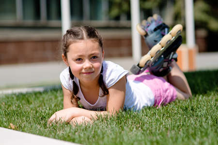 sward: Little girl in rollers is laying on the lawn in the park having rest