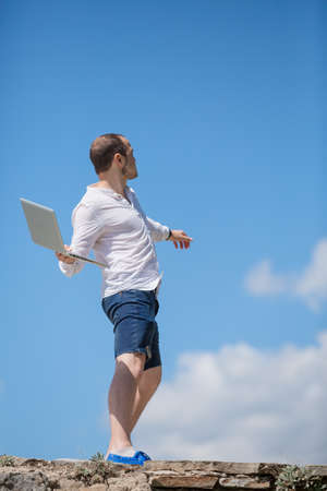 young man throws notebook against blue sky