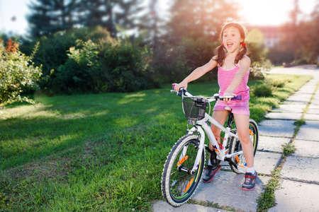 在夏天日落的愉快的儿童女孩骑马自行车在公园。活跃的孩子