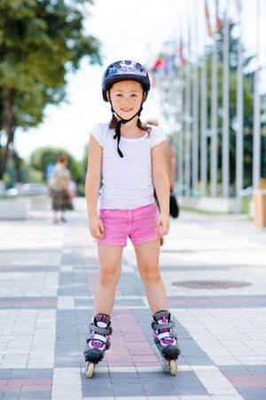 Little pretty girl on roller skates in helmet at a park. Front view