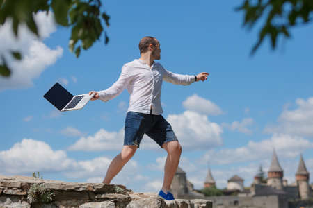 young man throws a laptop against blue sky Stock Photo