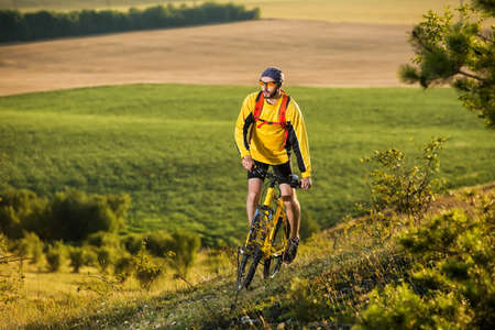 Young man cycling on a rural road through green summer meadow during sunset Stock Photo