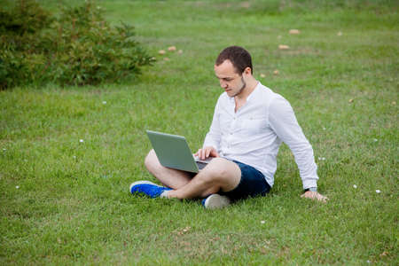people relaxing: A young man with laptop working outdoor
