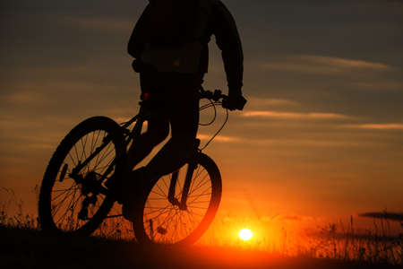 Silhouette of a bike on sky background on red sunset