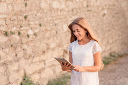 Young pretty woman in white dress using a tablet computer outside a building Stock Photo