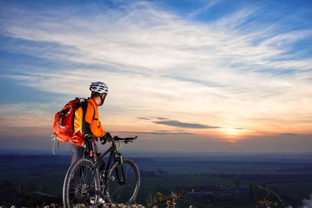 cyclist on mountain-bike at sunset, cyclist on the background of beautiful sunset. cyclist with white helmet and red backpack. beautiful landscape. back view. Standard-Bild