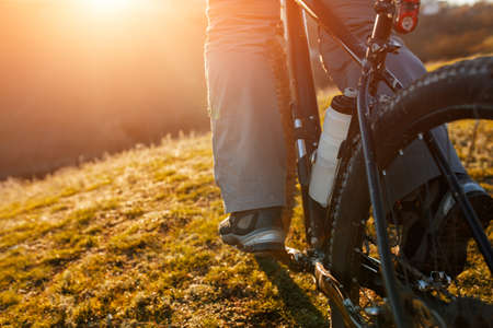 horisontal: low angle view of cyclist standing with mountain bike at sunrise against bright sun and blue sky. sping season. Horisontal wide angle fisheye photo