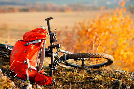Mountain bike after ride in nature with backpack. Stock Photo