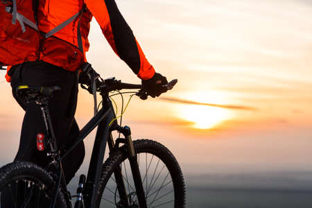 rapidity: cyclist on mountain-bike at sunset, cyclist on the background of beautiful sunset.