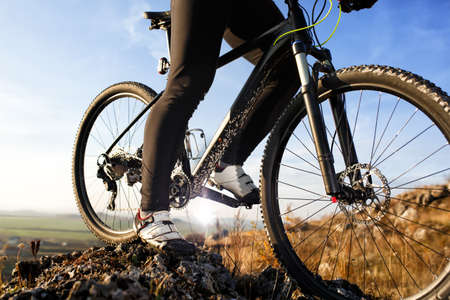 Closeup of cyclist man legs riding mountain bike on outdoor trail on hill