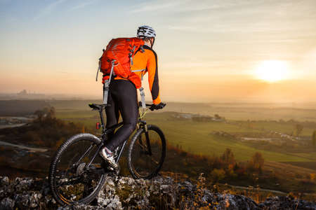 freeride: A cyclist with a backpack on a background of blue sky and the field.