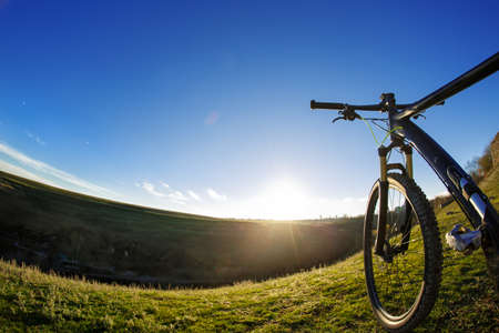 Mountain bike on journeys. Going up hills on small roads between green fields with blue sky. Stock Photo