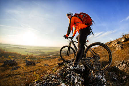 mountainbike: Cyclist on the top of a hill with blue sky clouds Stock Photo