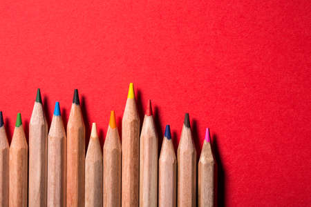 irregularity: line of colored pencils on bright red background. Creative location. Irregularity. Art and design. Idea and concept. Drawing and painting.