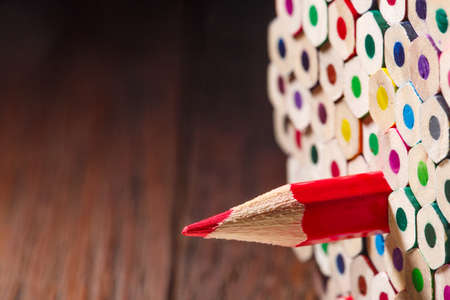 Pack of color pencils with a single sharp one symbolizing leadership concept