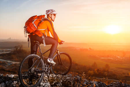 red mountain: Cyclist with mountain bike on top observing the view. At sunset with lens flare