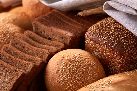 Assortement of Freshly baked traditional bread with ears of wheat and white cloth Stock Photo