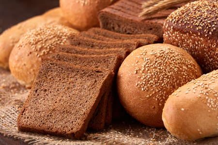 Assortement of bread on burlap on the wooden table. Slices of bread and roll.