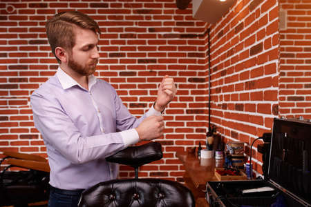 fastens: Portrait of the hairdresser. Cheerful young bearded man fastens the buttons on the sleeve on his shirt. Stock Photo