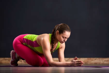 Portrait of beautiful young woman working out against dark wall, doing yoga or pilates exercise.