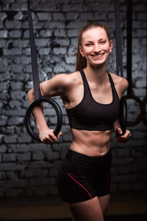 Fit young sporty woman holding gymnast rings and smiling at the cross fit gym against brick wall.