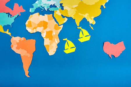 World map cut out of colored paper and two cut out of yellow paper ships based on blue.