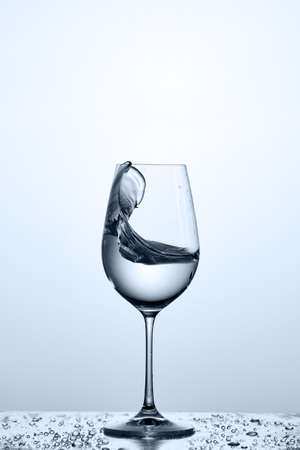 Splashing cleaner water wave in the wineglass while standing on the glass with drapes against light background. Stock Photo